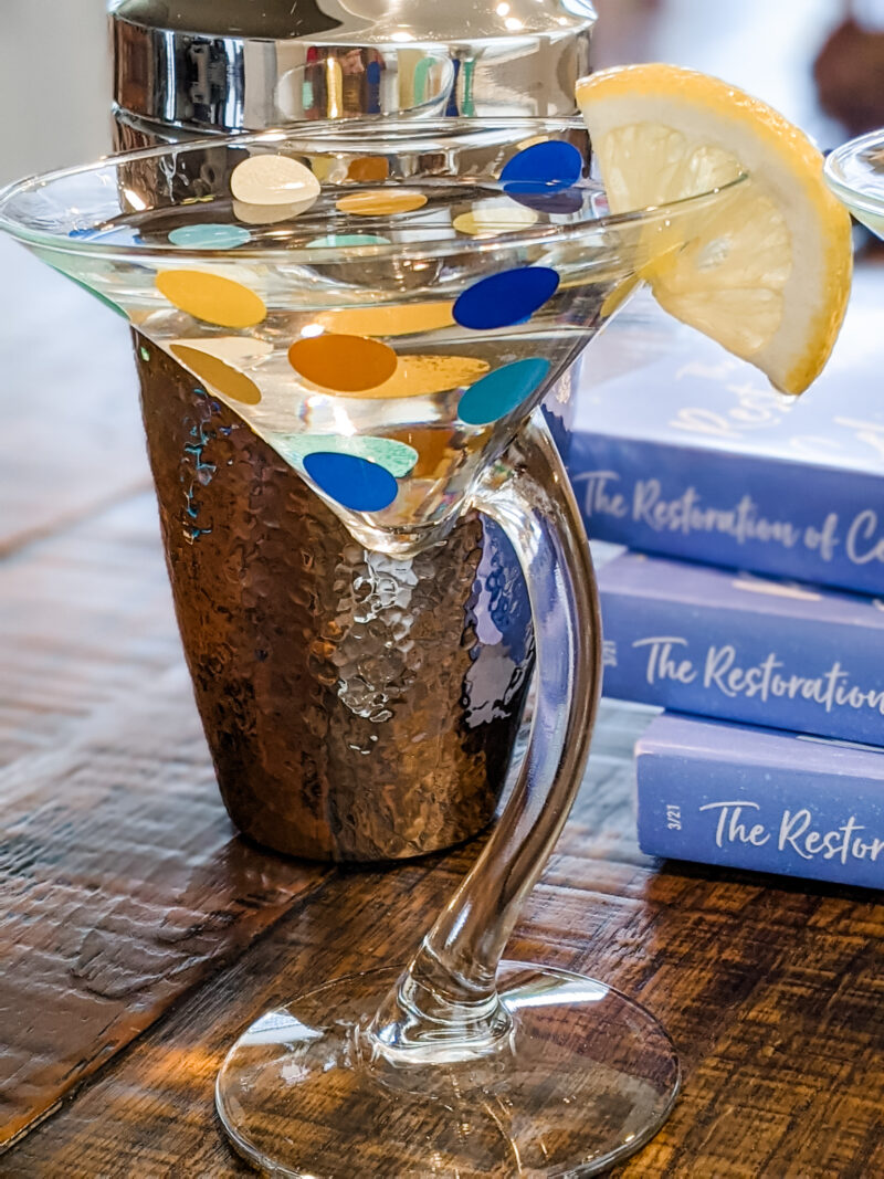 The finished DIY Polka Dot Martini Glasses with a lemon wedge, in front of The Restoration of Celia Fairchild paperbacks