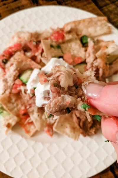 A hand holding a piece of the Healthier Chicken Nachos above a plate of them.