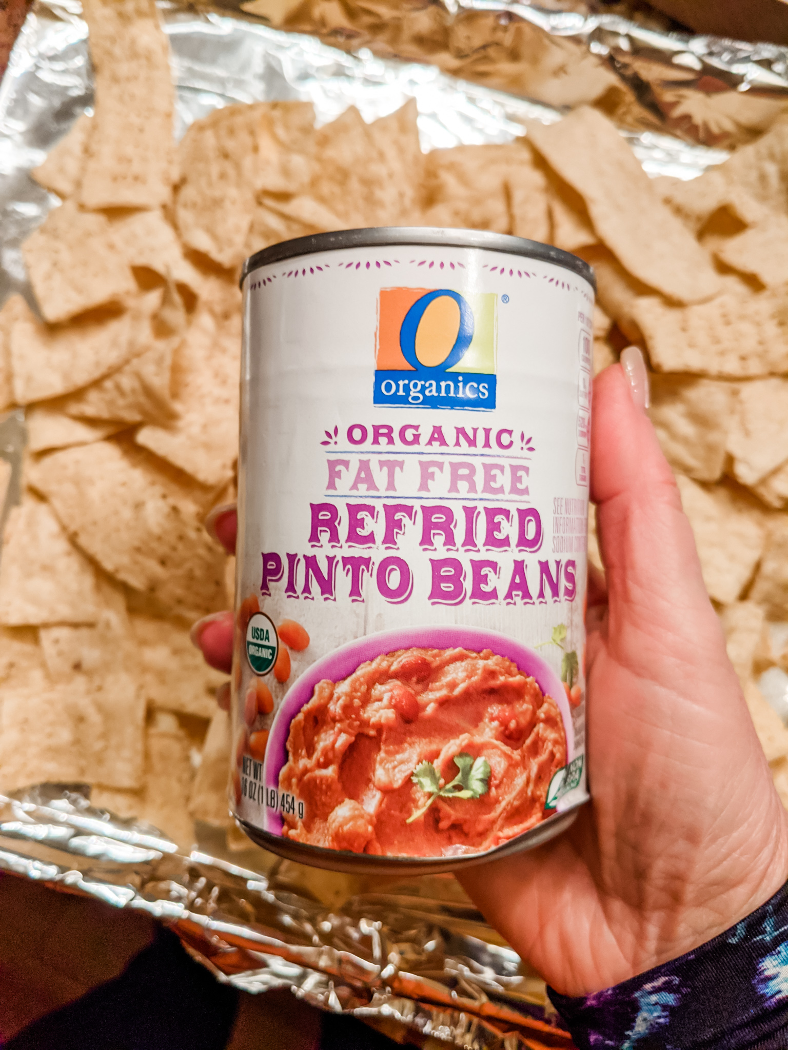 A can of refried beans held above a try filled with tortilla chips