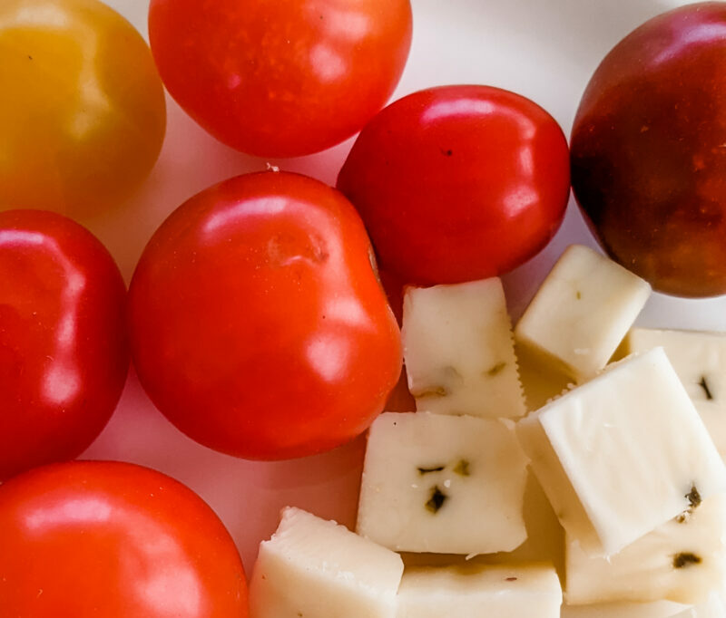 Cherry tomatoes and cubed pepperjack cheese together on a white plate.