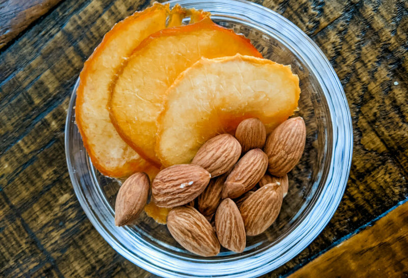 Dried peaches and almonds nestled into a clear container - a perfect and easy healthy snack from home