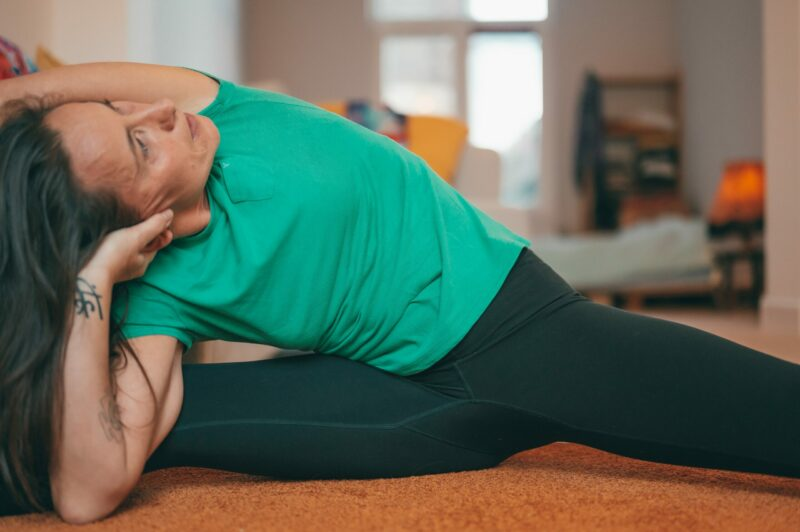 An older woman in workout gear doing a side stretch