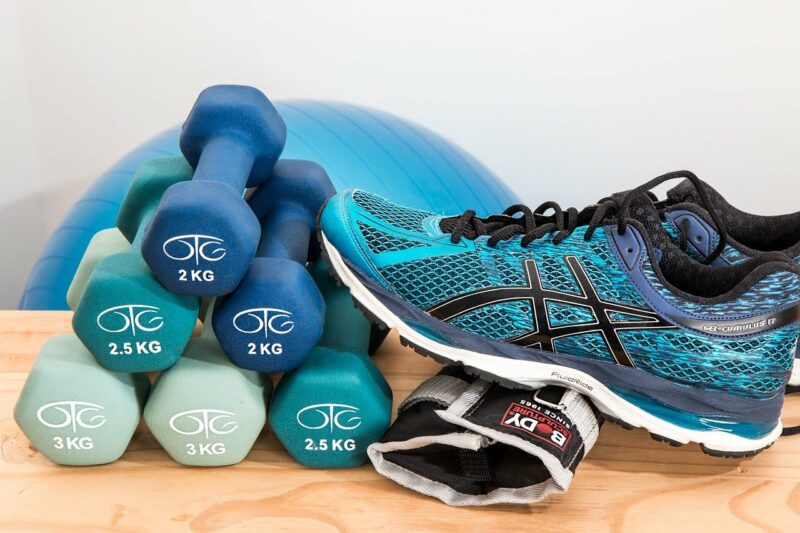 A collection of workout equipment - weights, shoes, ball - all of which are blue