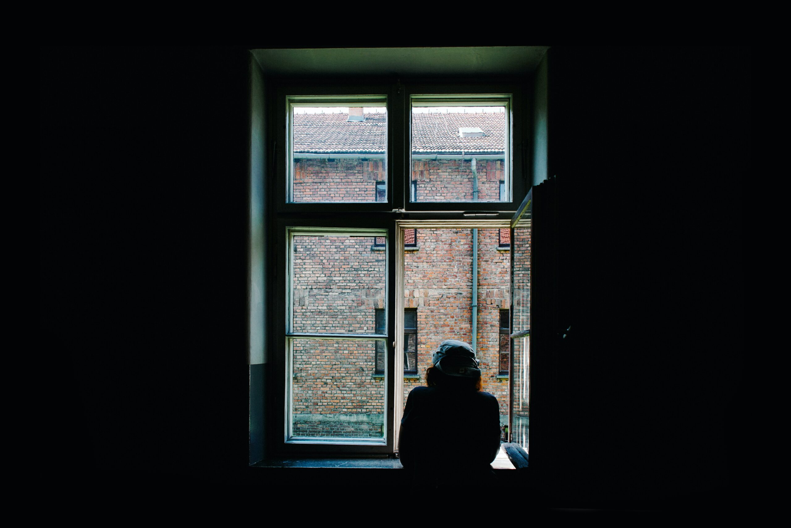 A woman looks out a window, bringing reflections of a different resolution for 2021