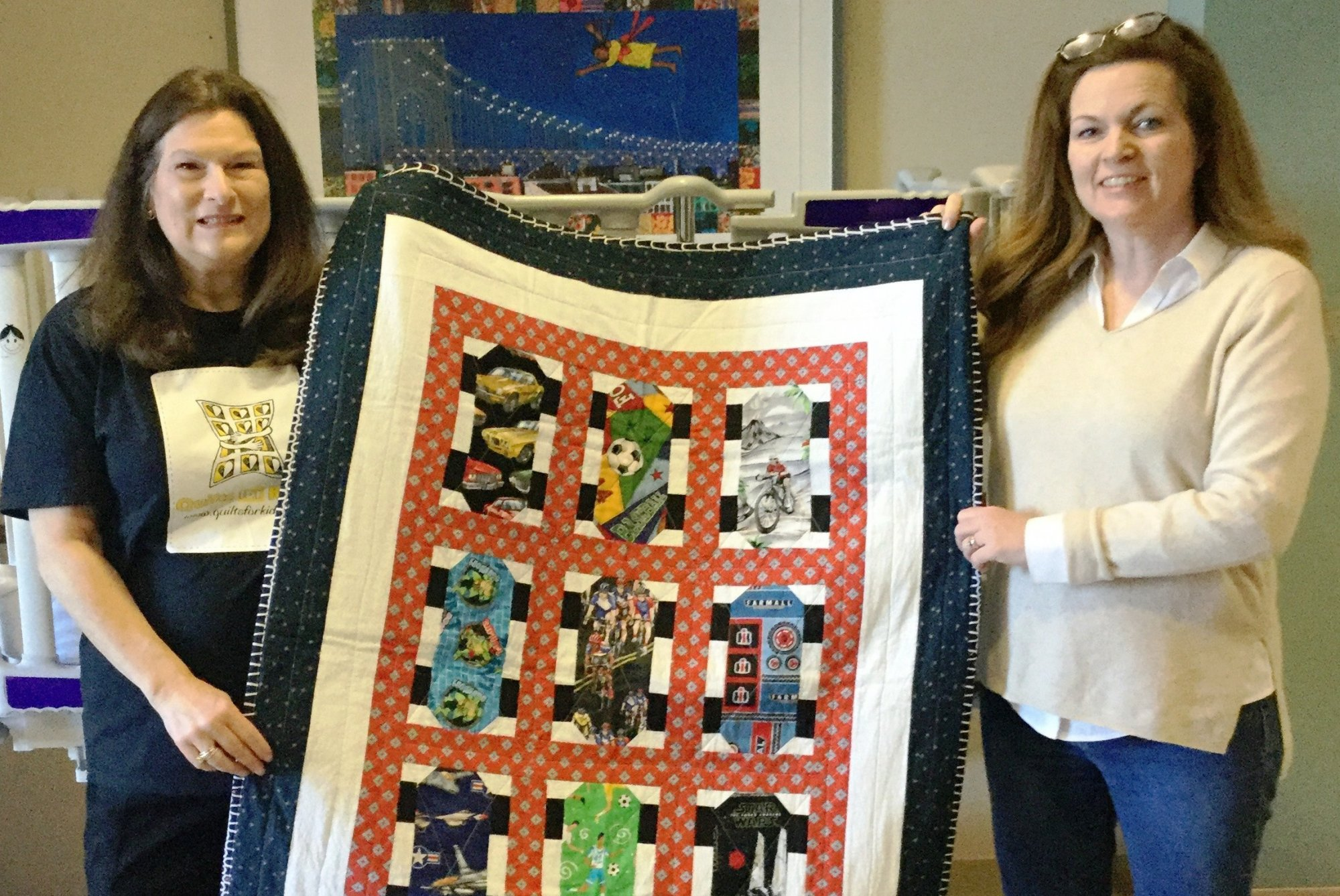 Marie and a volunteer stand, holding a quilt