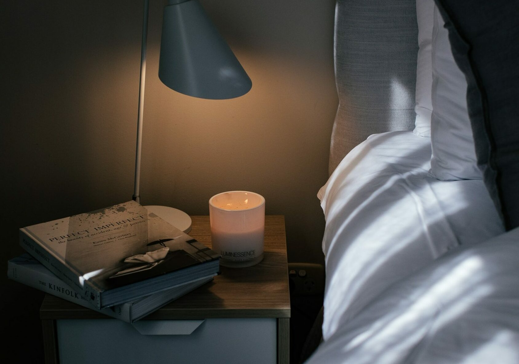A bedside with diffused soft lighting and candle - a way to treat insomnia naturally