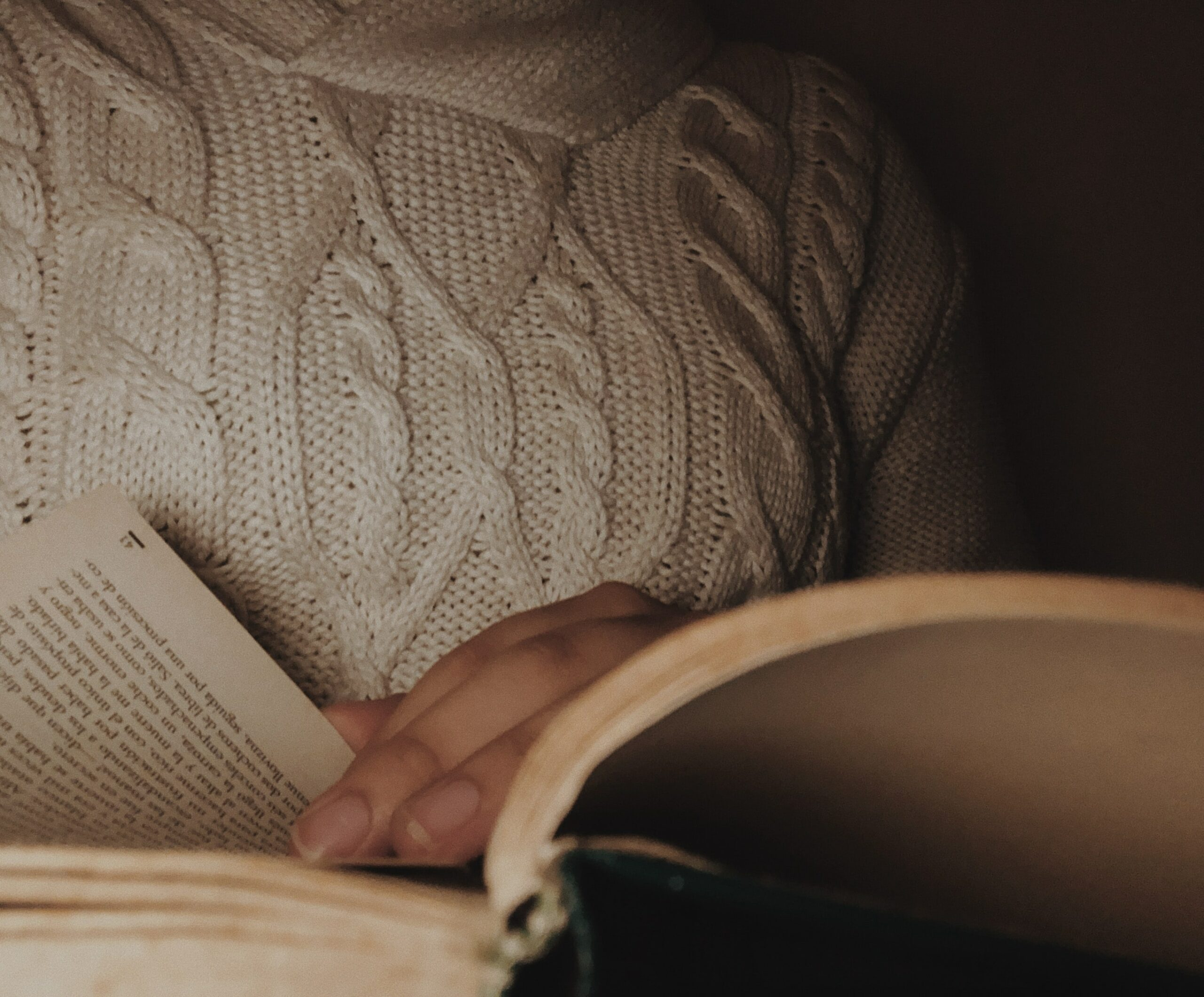 A woman reading a book in dim lighting - taking a break from trying to sleep, a way to treat insomnia naturally