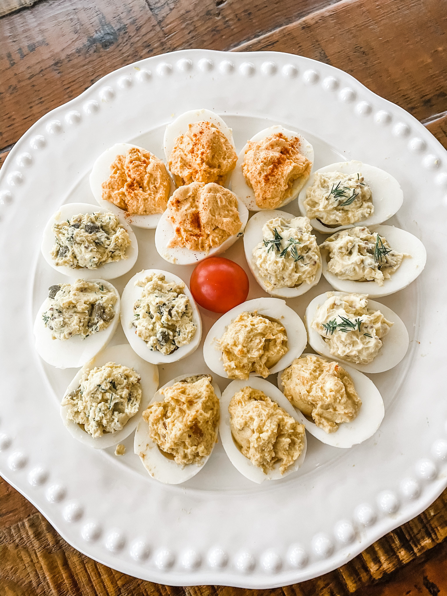 All four variations of the lighter deviled eggs on a white plate.