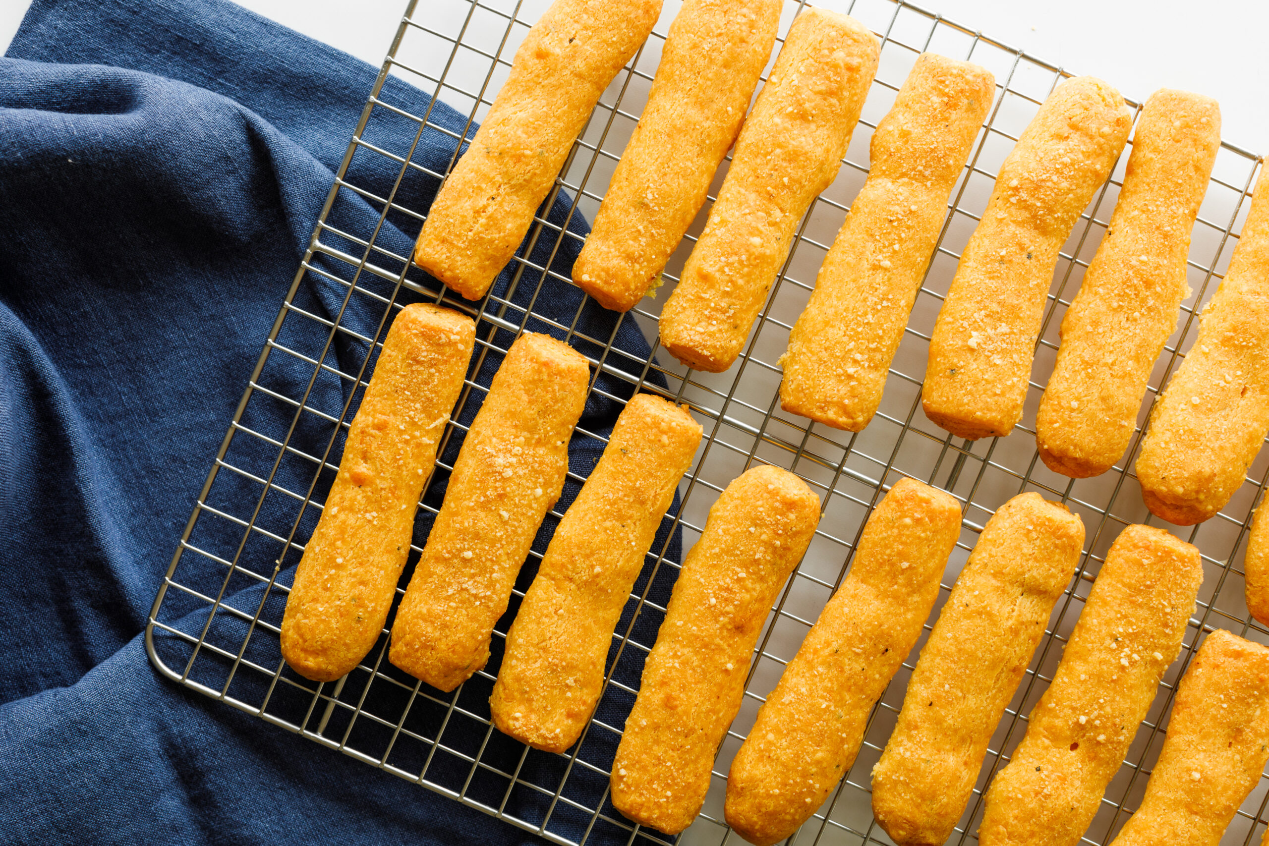 The finished cheese sticks on a cooling rack on top of a blue tablecloth.