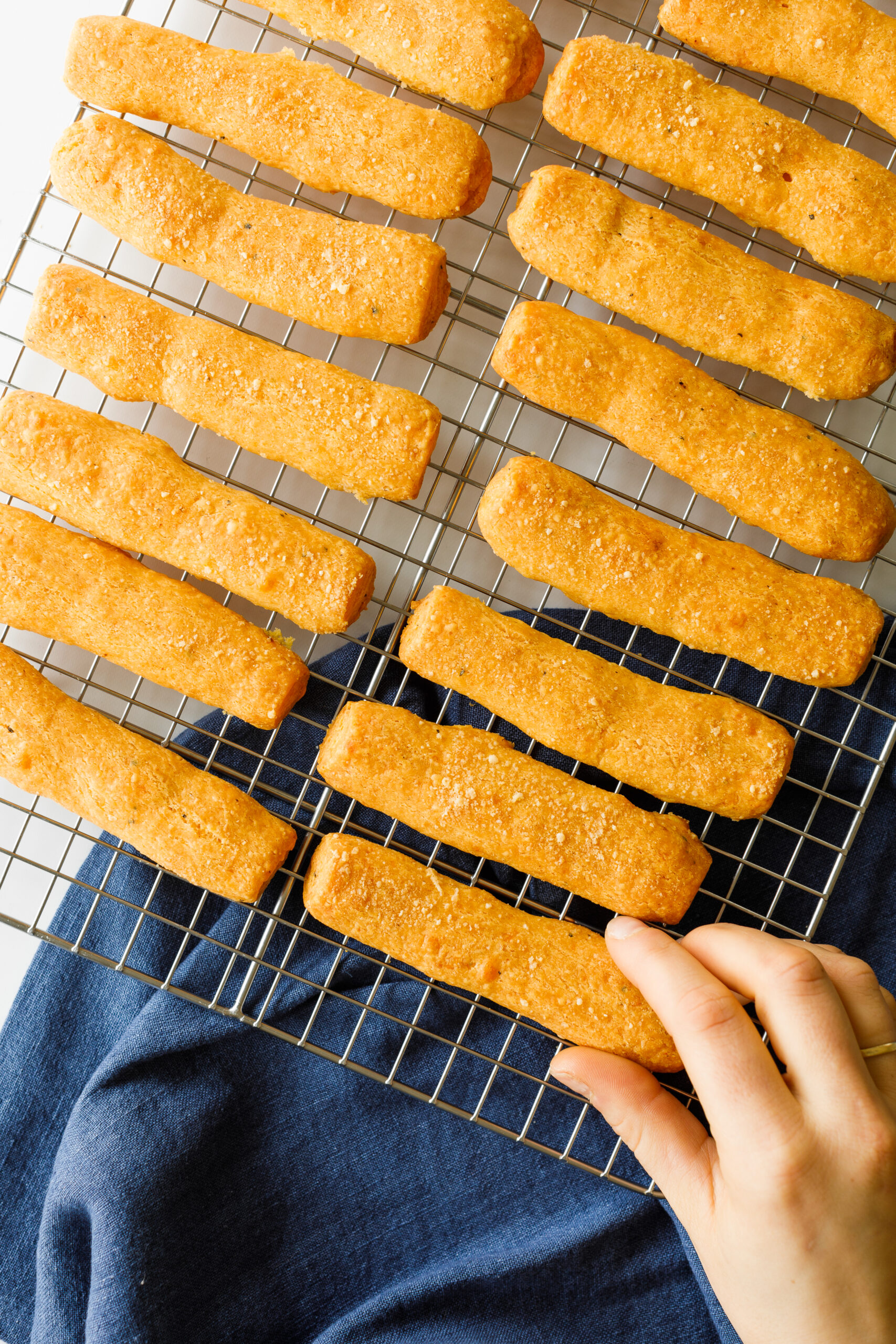 The Parmesan and Sharp Cheddar Cheese Straws on a cooling rack, with a hand reaching for one.