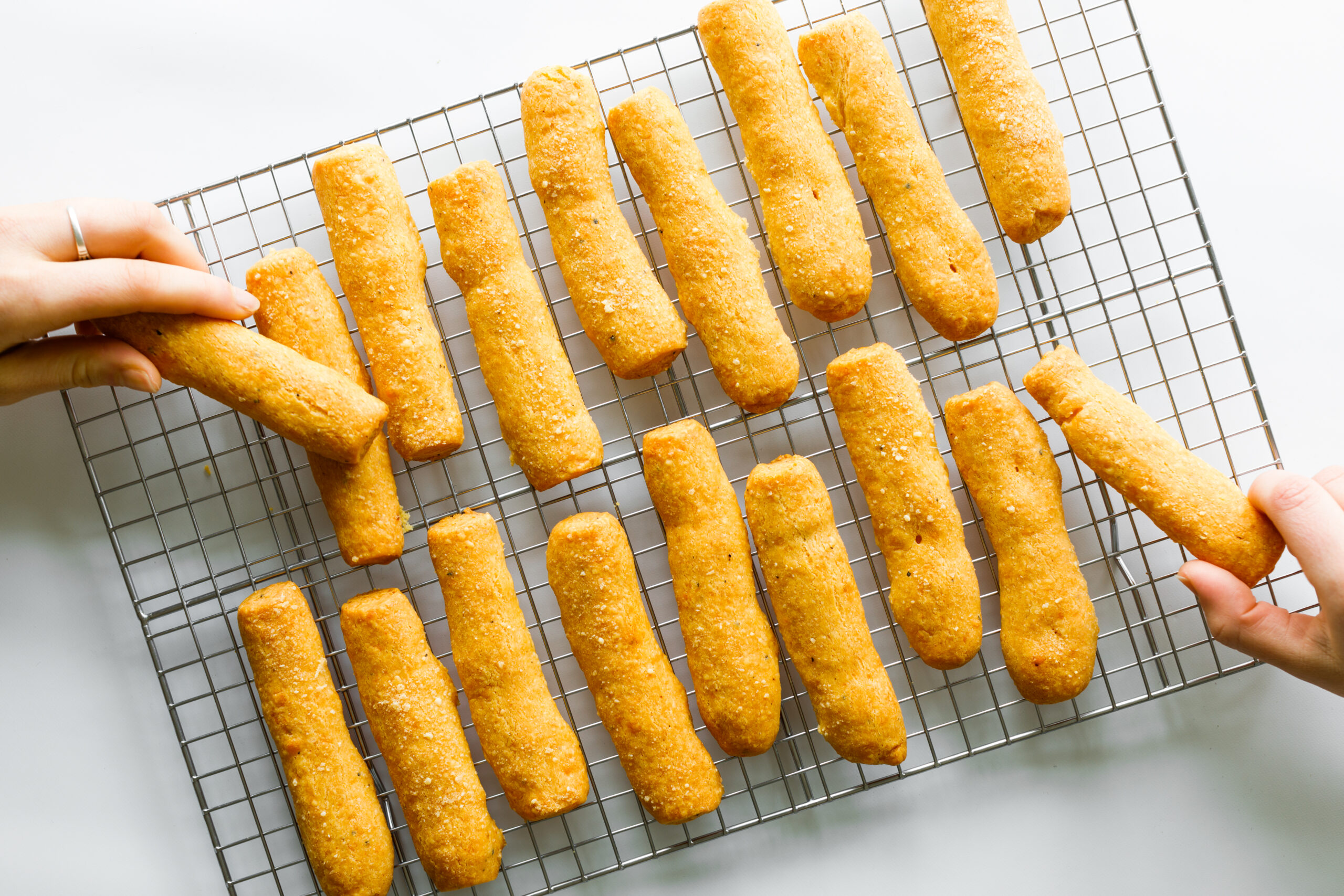 The Parmesan and Sharp Cheddar Cheese Straws, with two hands picking some off