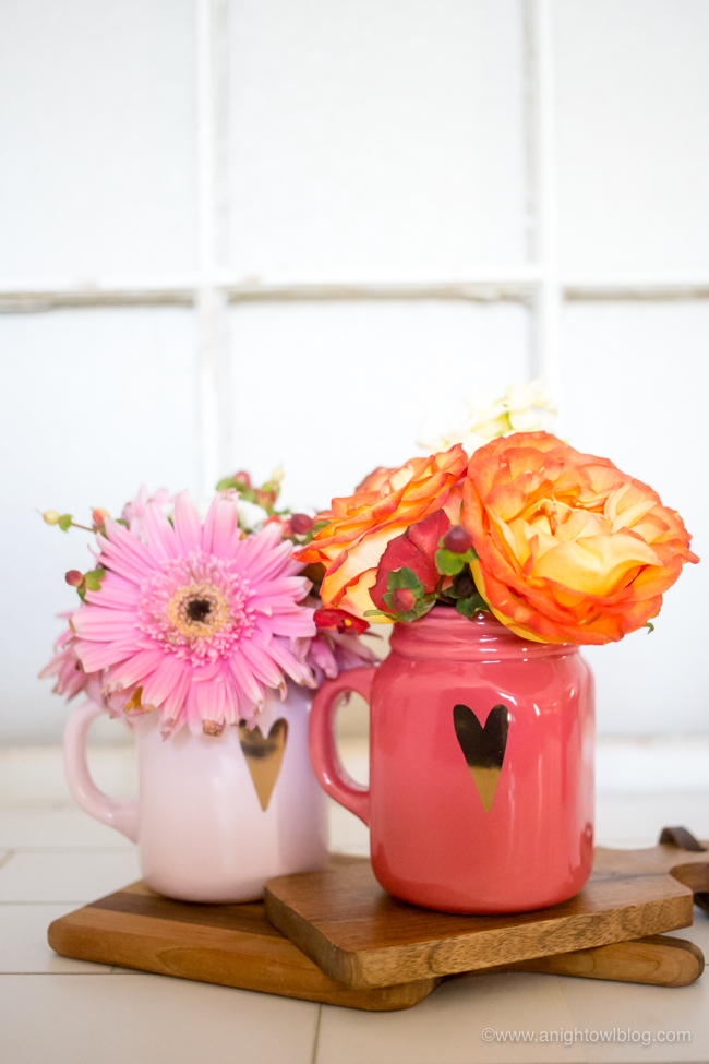 Two mugs with hearts with flowers arranged in it.
