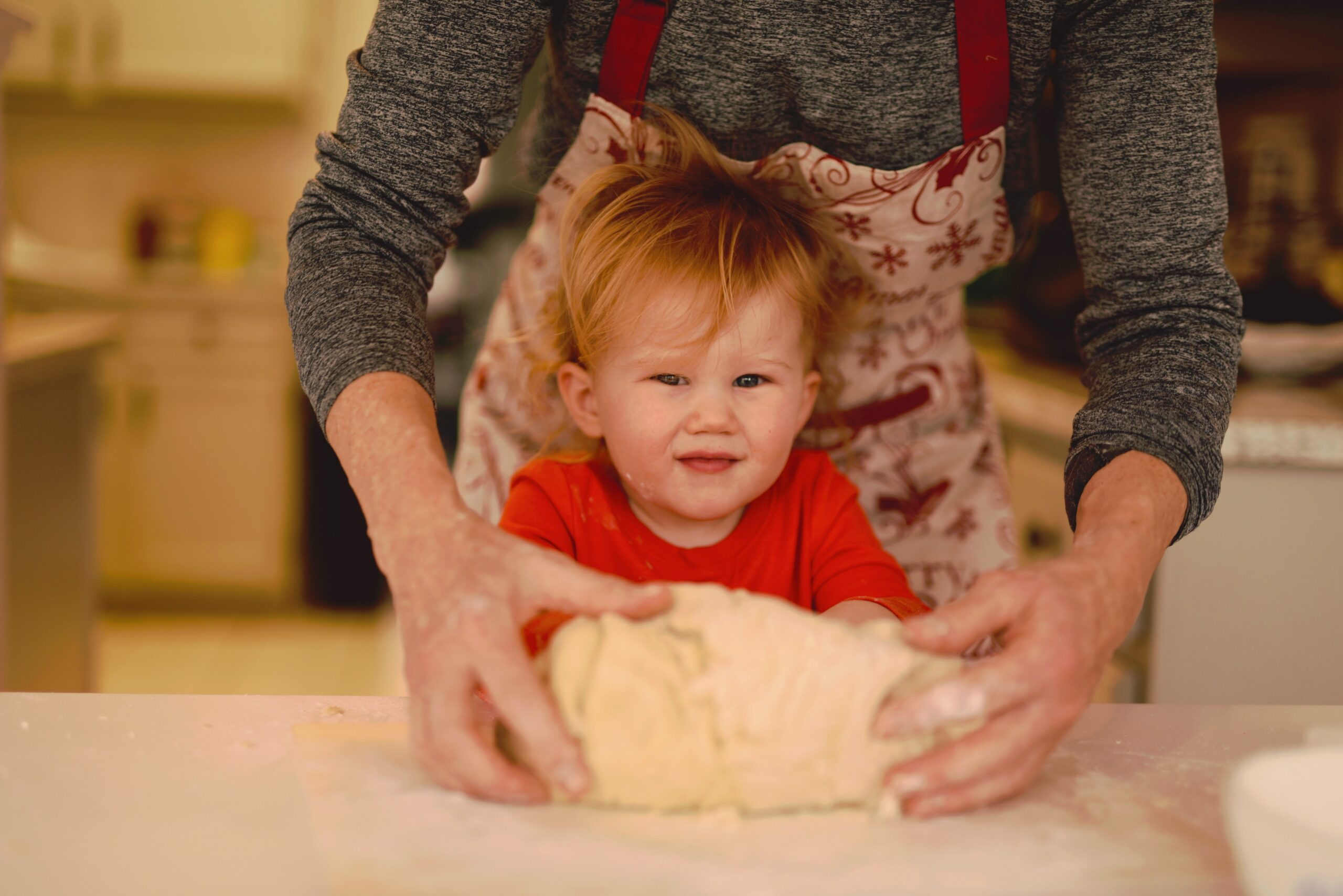 A woman kneads bread with a toddler.
