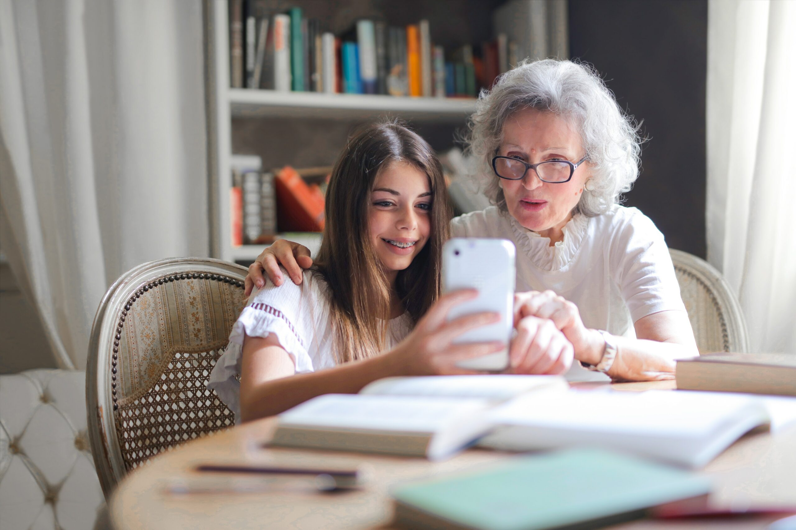 A woman and her granddaughter look at a phone together - one of the most well-known ways of of keeping in touch with kids