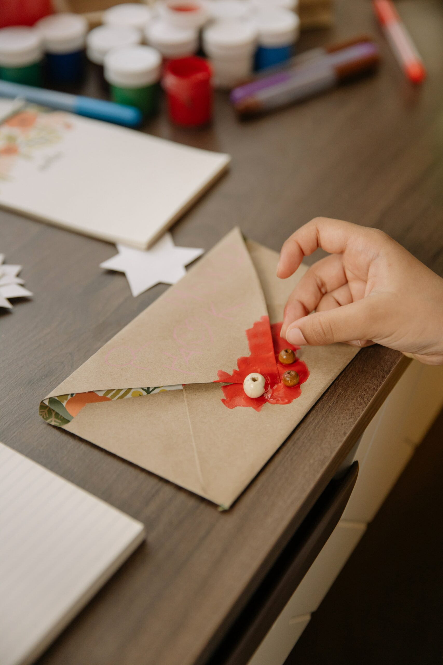 A small hand glues a bead on to a hand-decorated brown envelope, with crafting supplies in the background - a great way of keeping in touch with kids