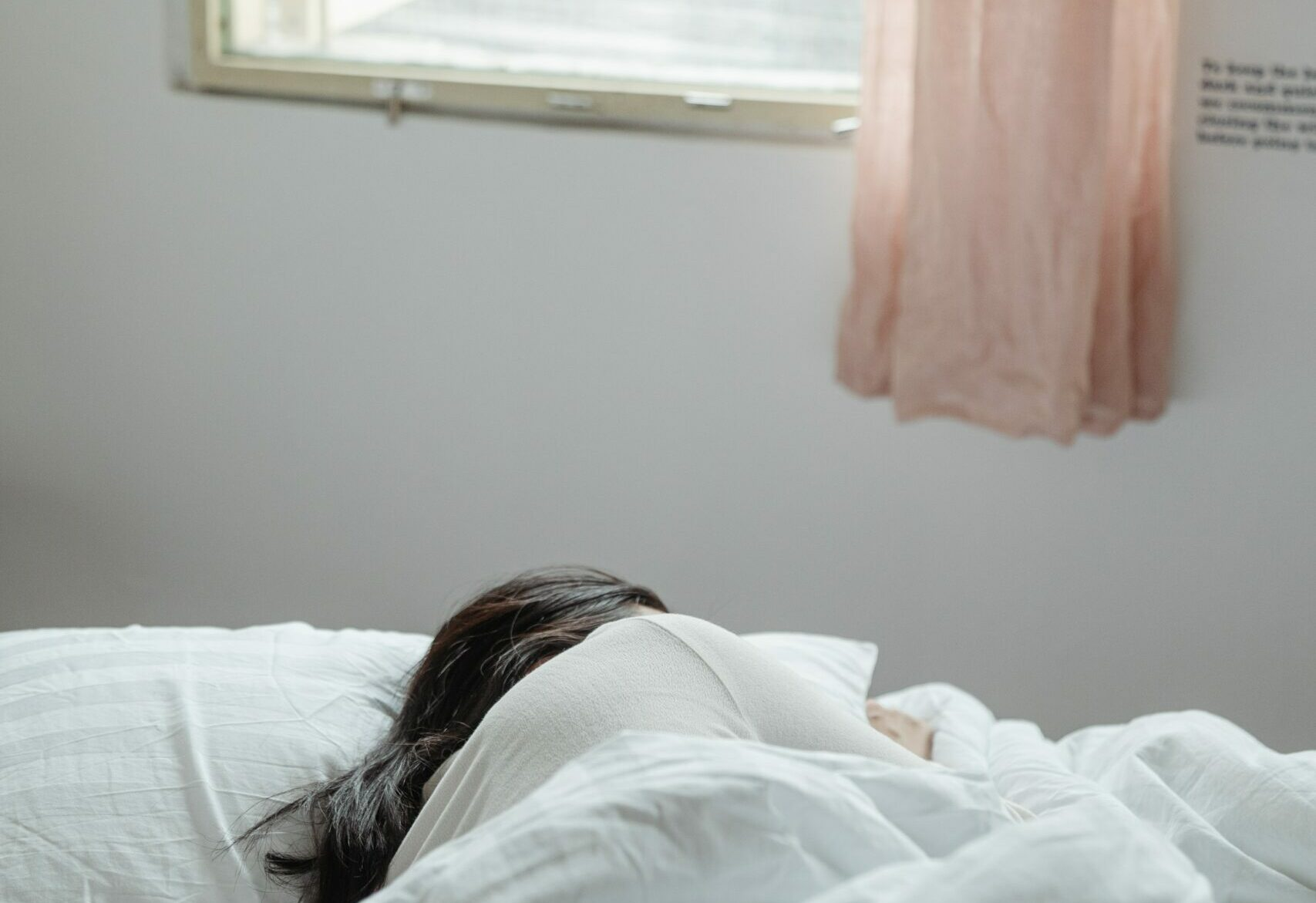 A woman sleeping on her side in a bed with light coming through a window - a way to treat insomnia naturally