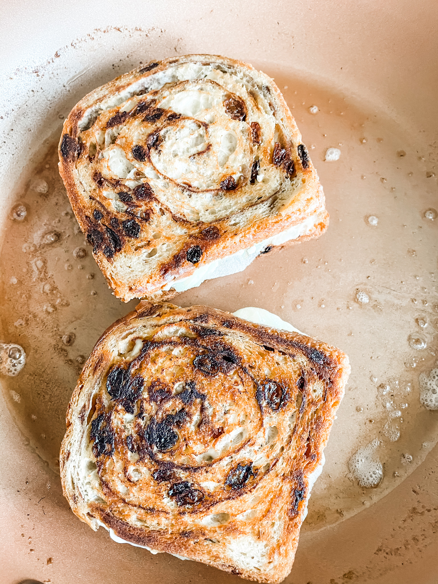 The Grilled Apple and Brie Cheese Sandwiches being toasted in a buttered pan