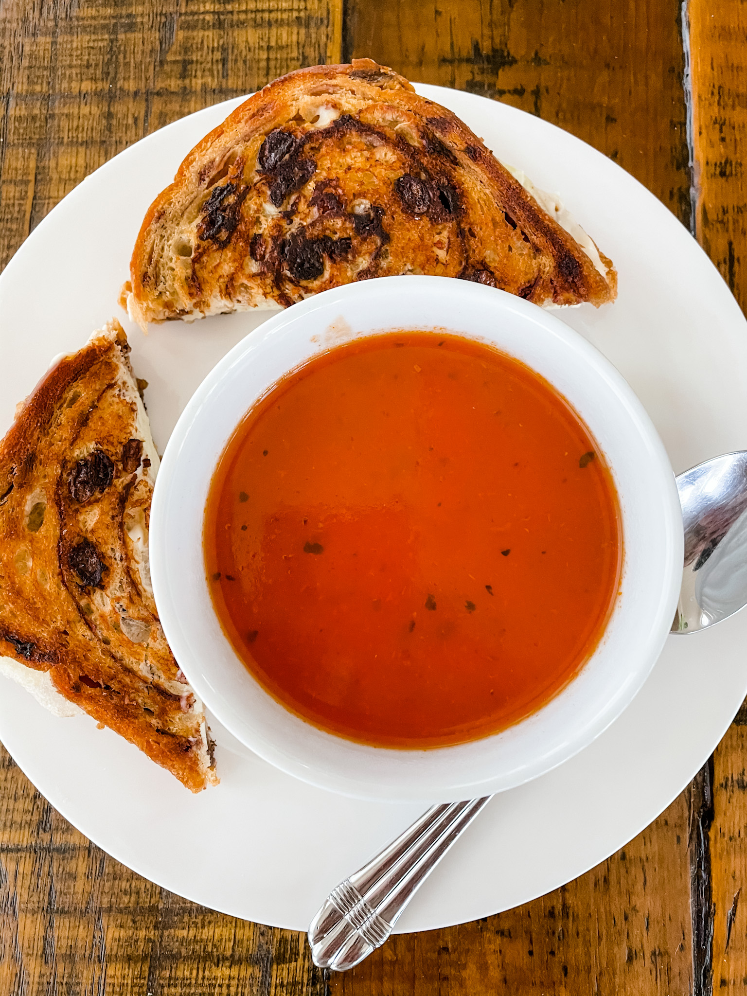 A cut in half Grilled Apple and Brie Cheese Sandwiches placed next to the bowl of tomato soup