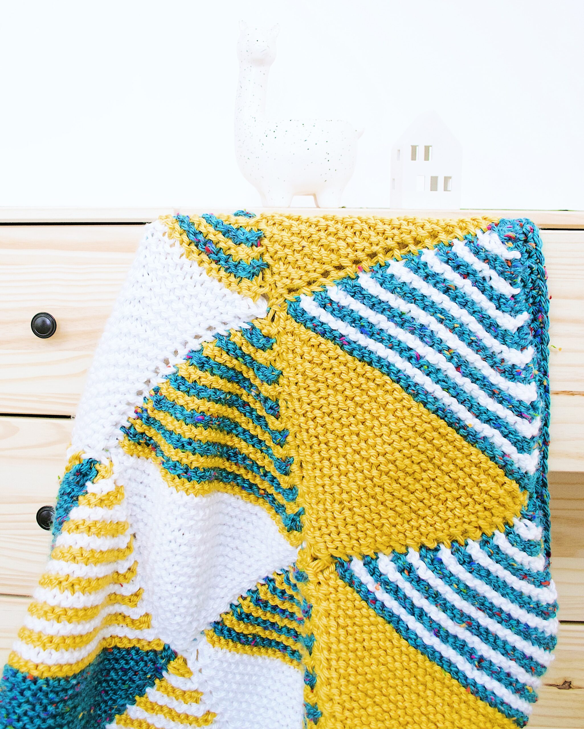 The Knitted Baby Blanket draped over a wooden set of drawers