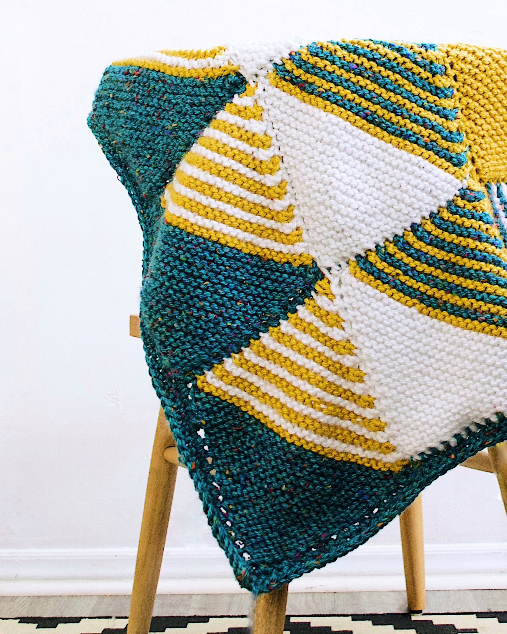The finished Knitted Baby Blanket draped over a chair