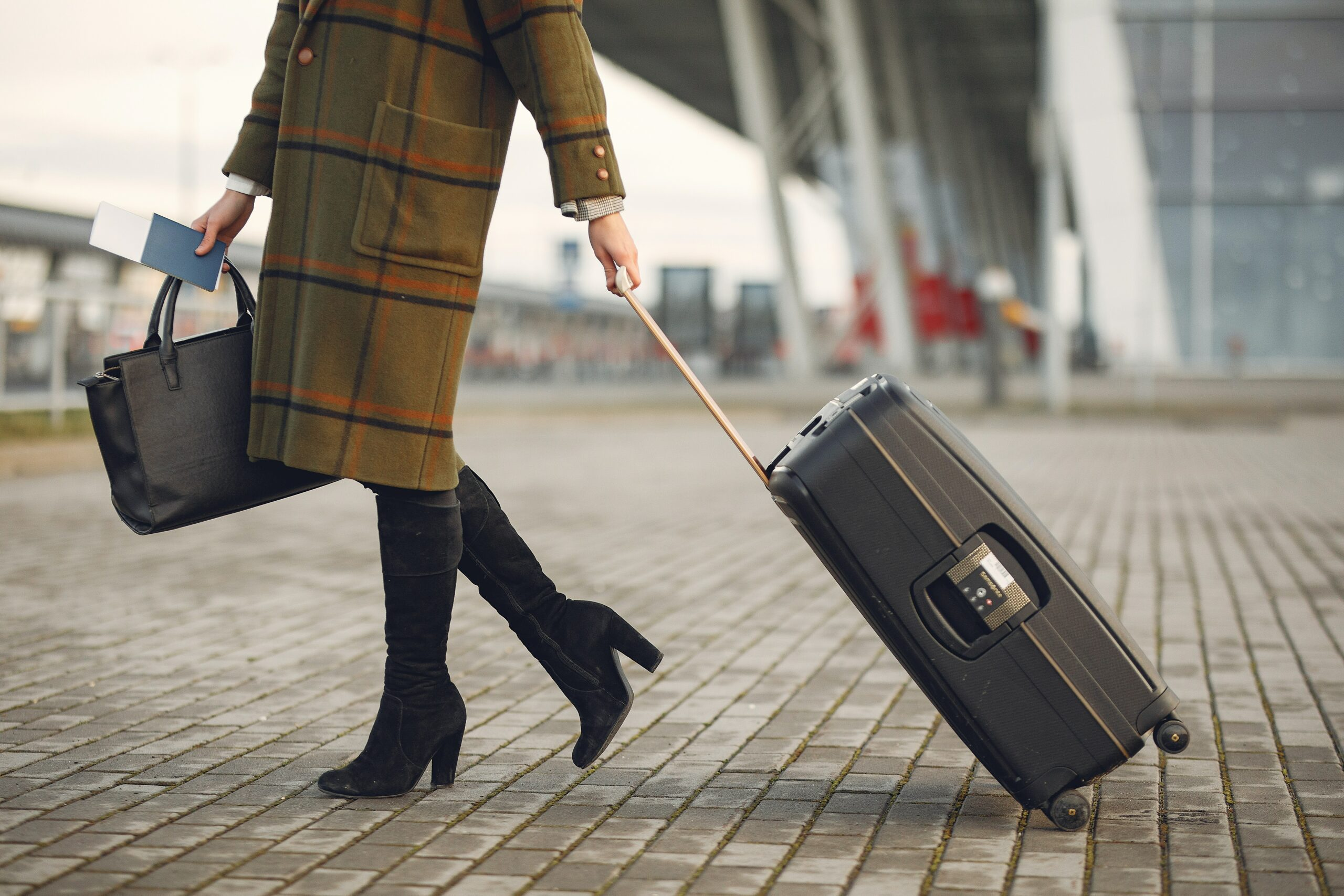 A woman with a handbag and a rolling carry on