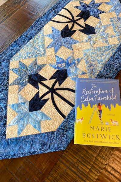A close up of the quilted table runner and the book that inspired it.