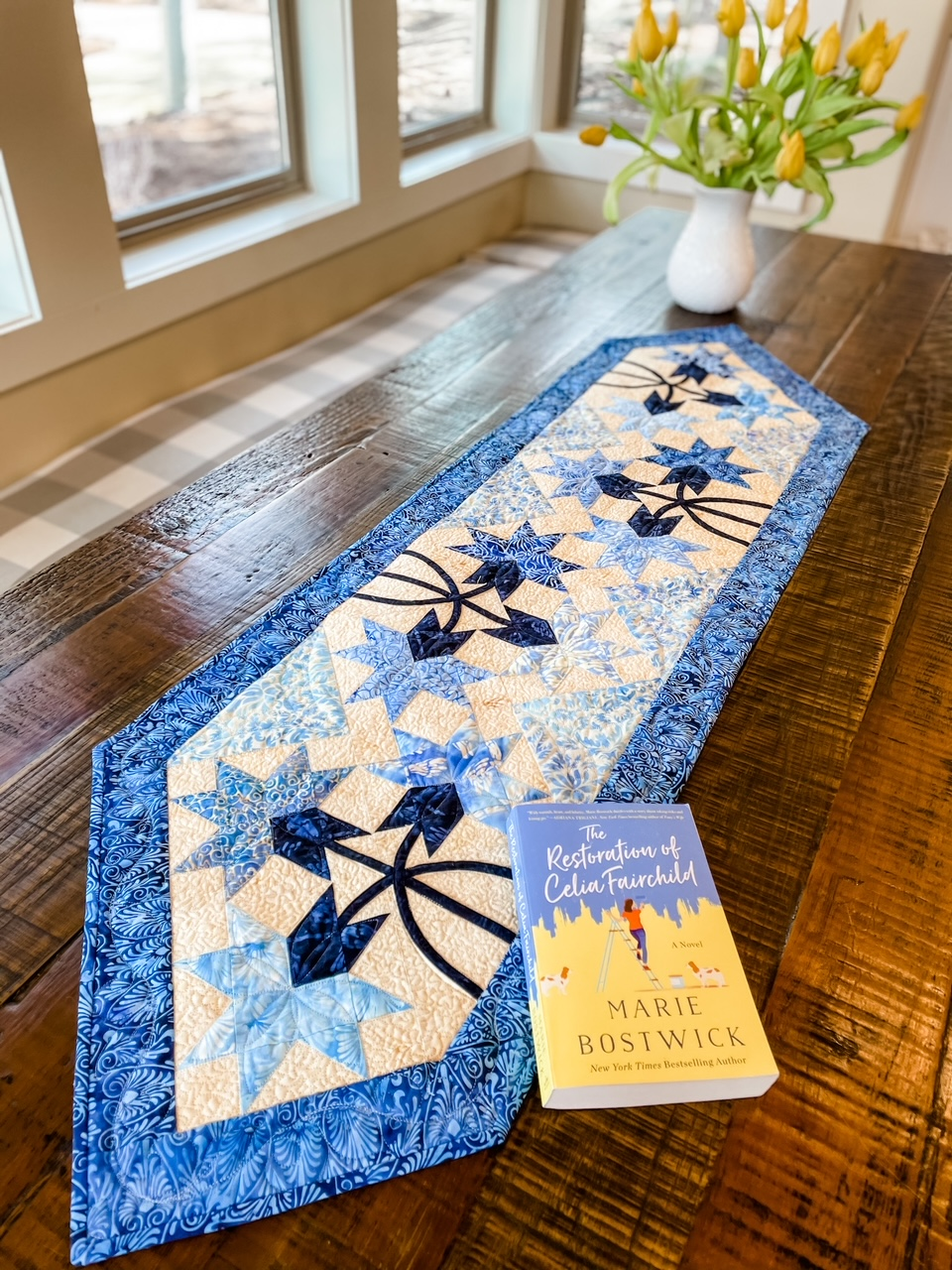 The quilted table runner on a wooden table, with Marie's novel and vase of flowers on top of it.