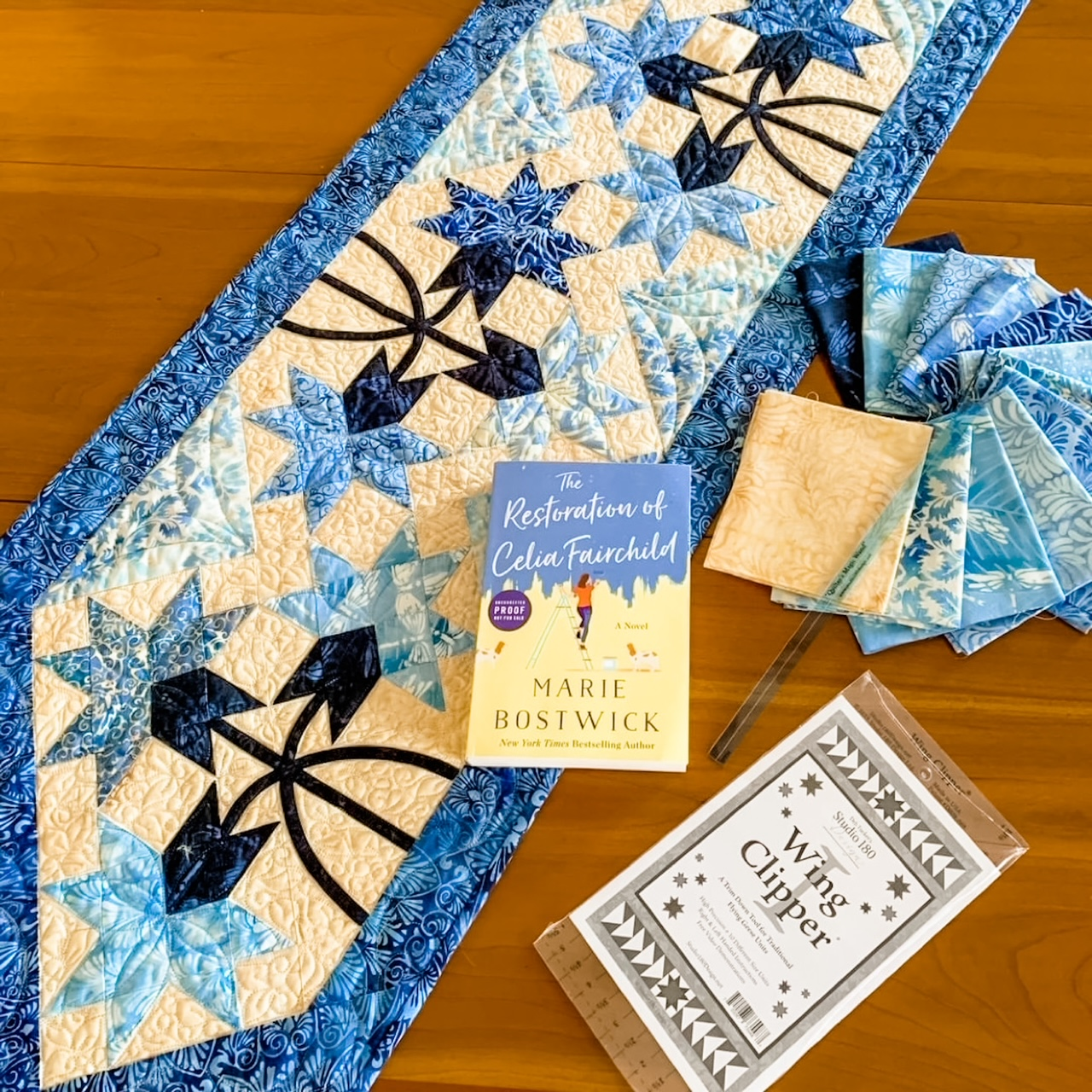 The quilted table runner with Marie's novel and fabric swatches surrounding it.