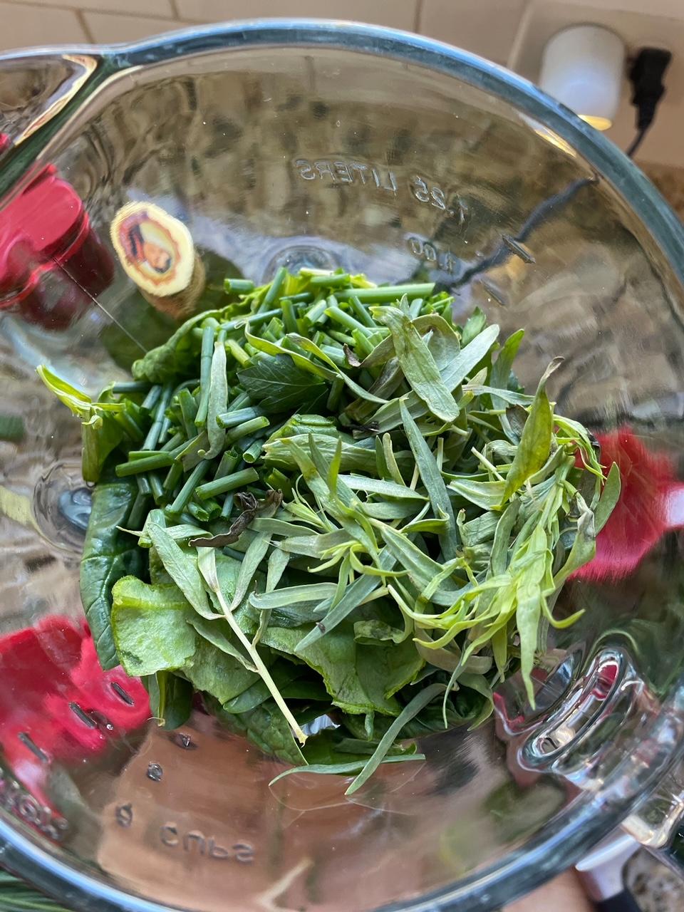 The greens for the Homemade Green Goddess Salad Dressing in a blender, not yet blended