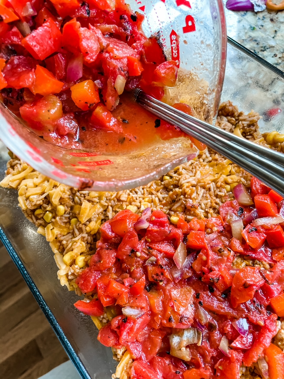 Diced tomatoes being poured into a baking dish