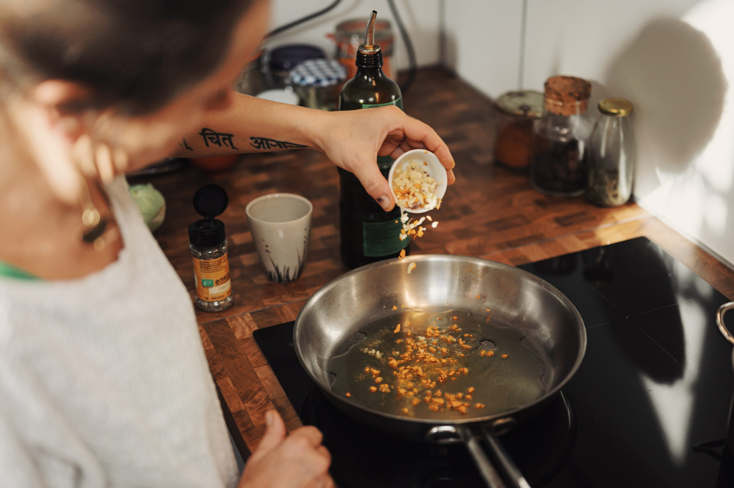 An older woman sprinkling pine nuts into a pan.