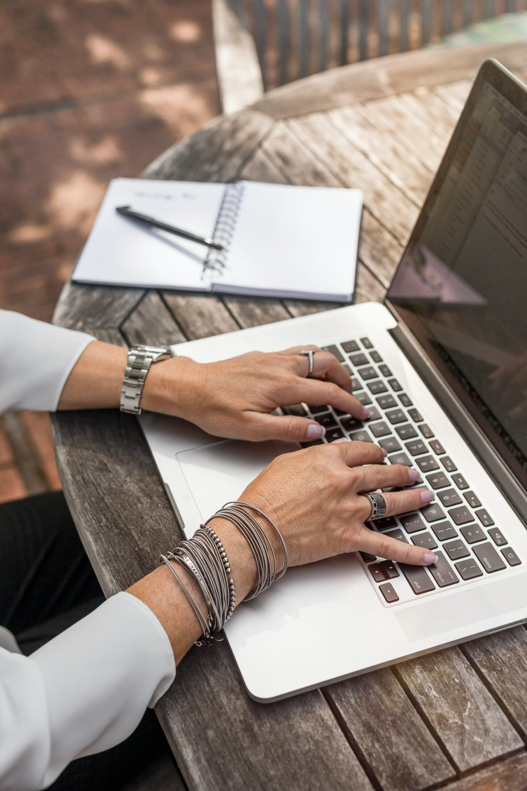 Dealing with Critic's Math: A woman types on a laptop outdoors