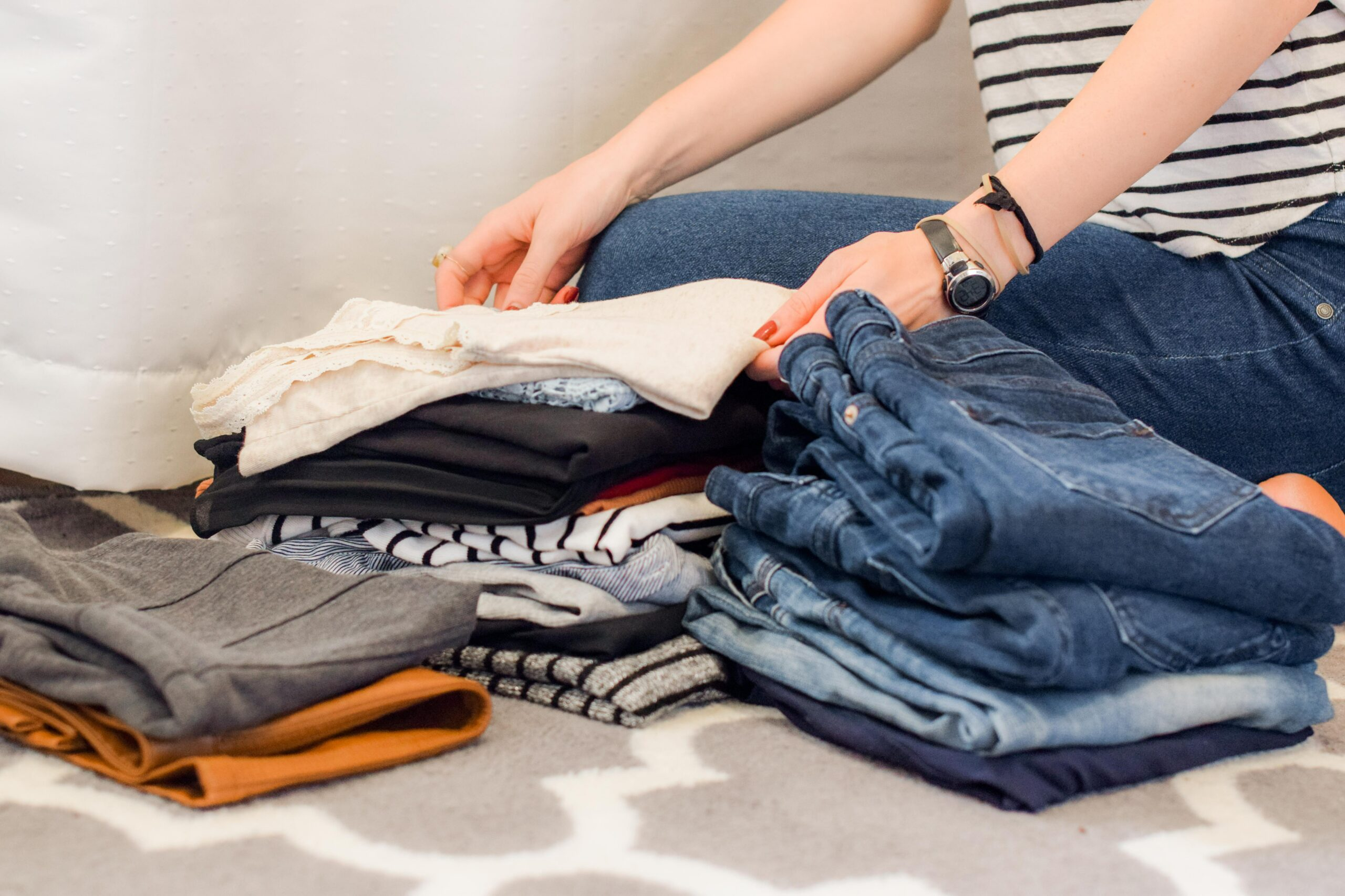 A woman sorting clothes - one of Marie's 10 Downsizing Tips and Truths