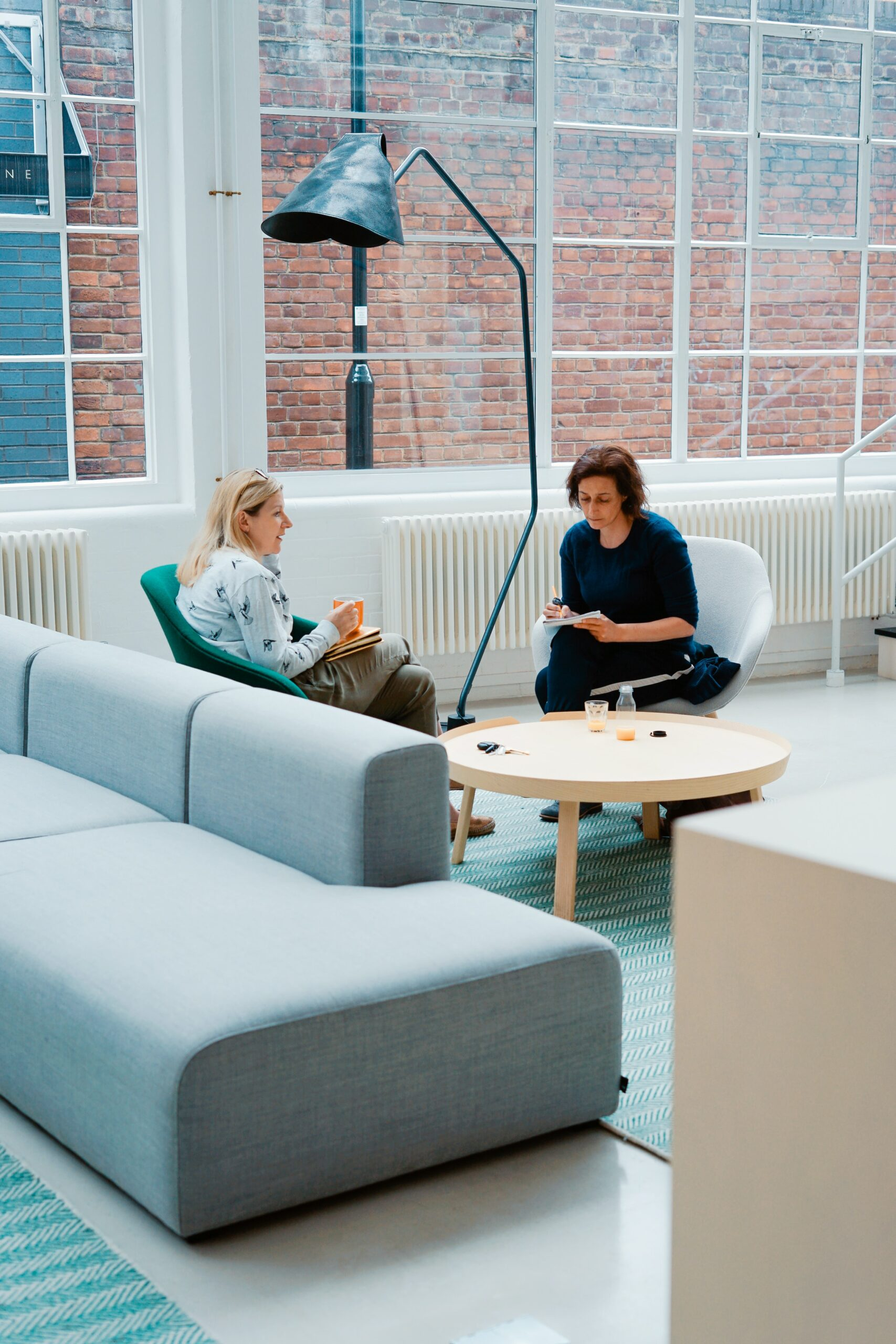 Two women in an office space having a discussion.