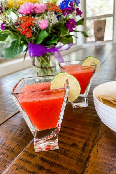 Two cups of the finished Fresh Strawberry Margaritas on a table
