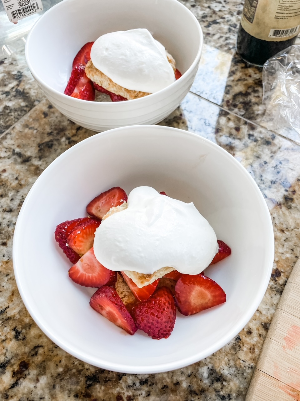 The finished Homemade Shortcake Biscuits topped with strawberries, whipped cream, served in white bowls