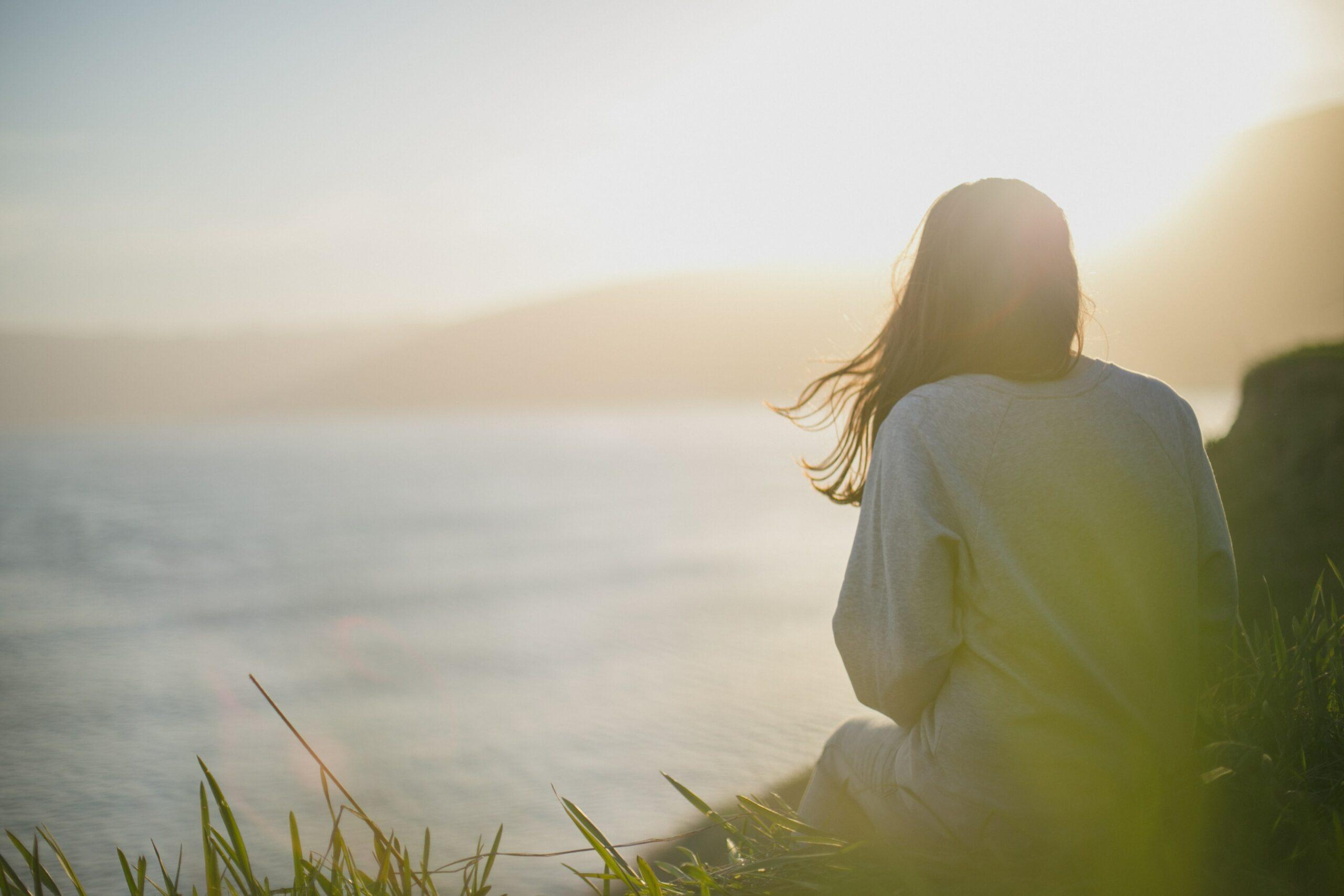 A woman watching a sunset on a beach