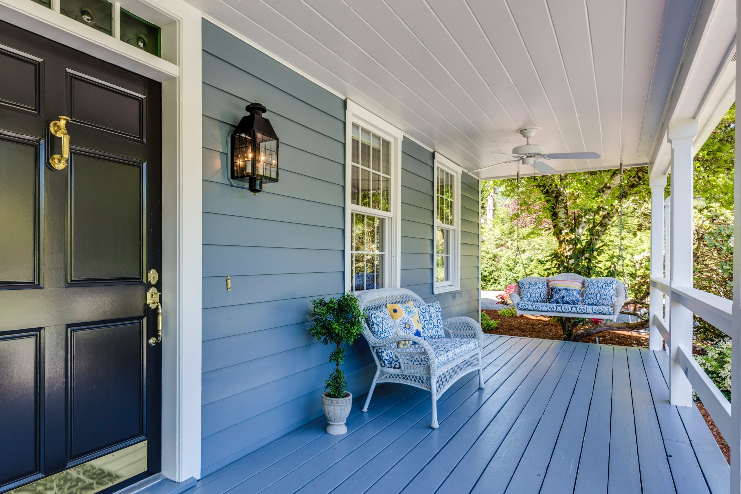 A front porch with a bench and potted plant
