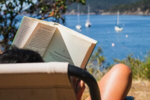 A woman reading a book in front of a marina - summer 2021 reading list