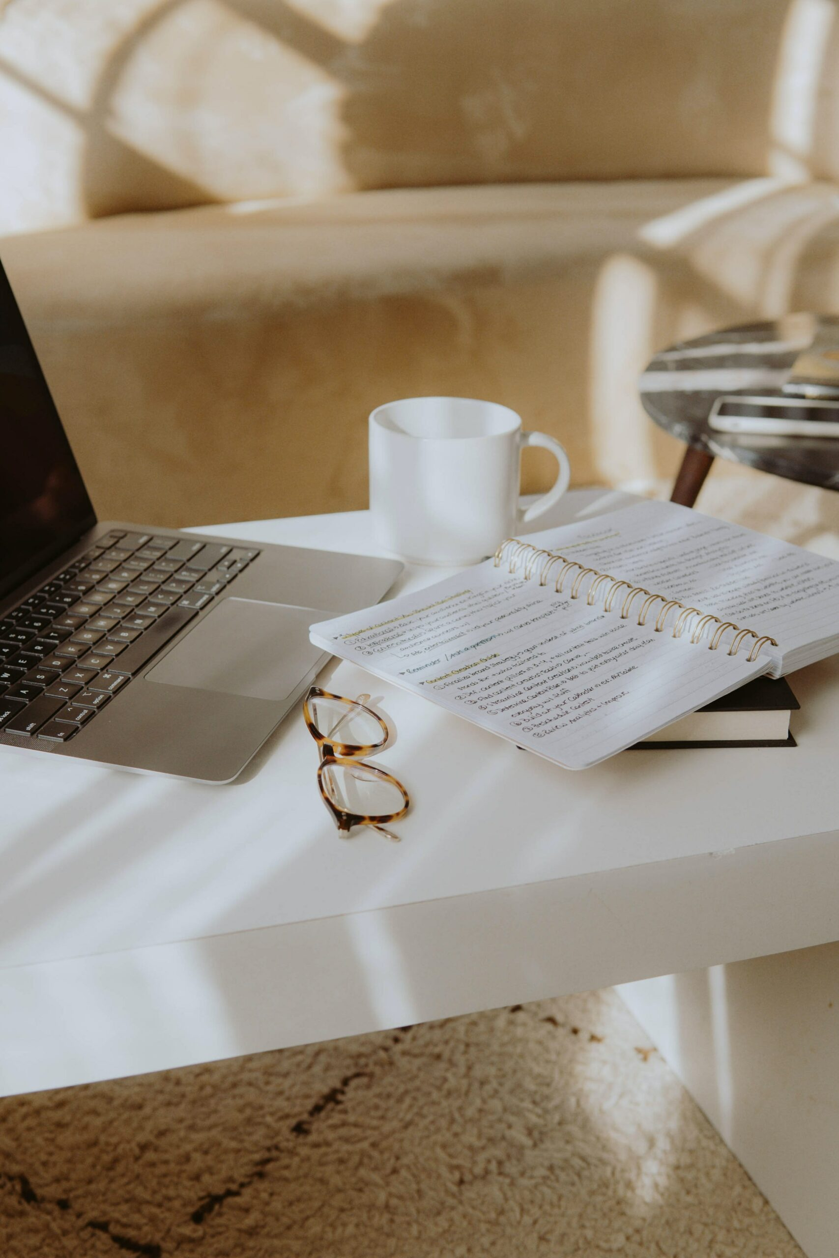 A table with a laptop, glasses, mug, and notebook