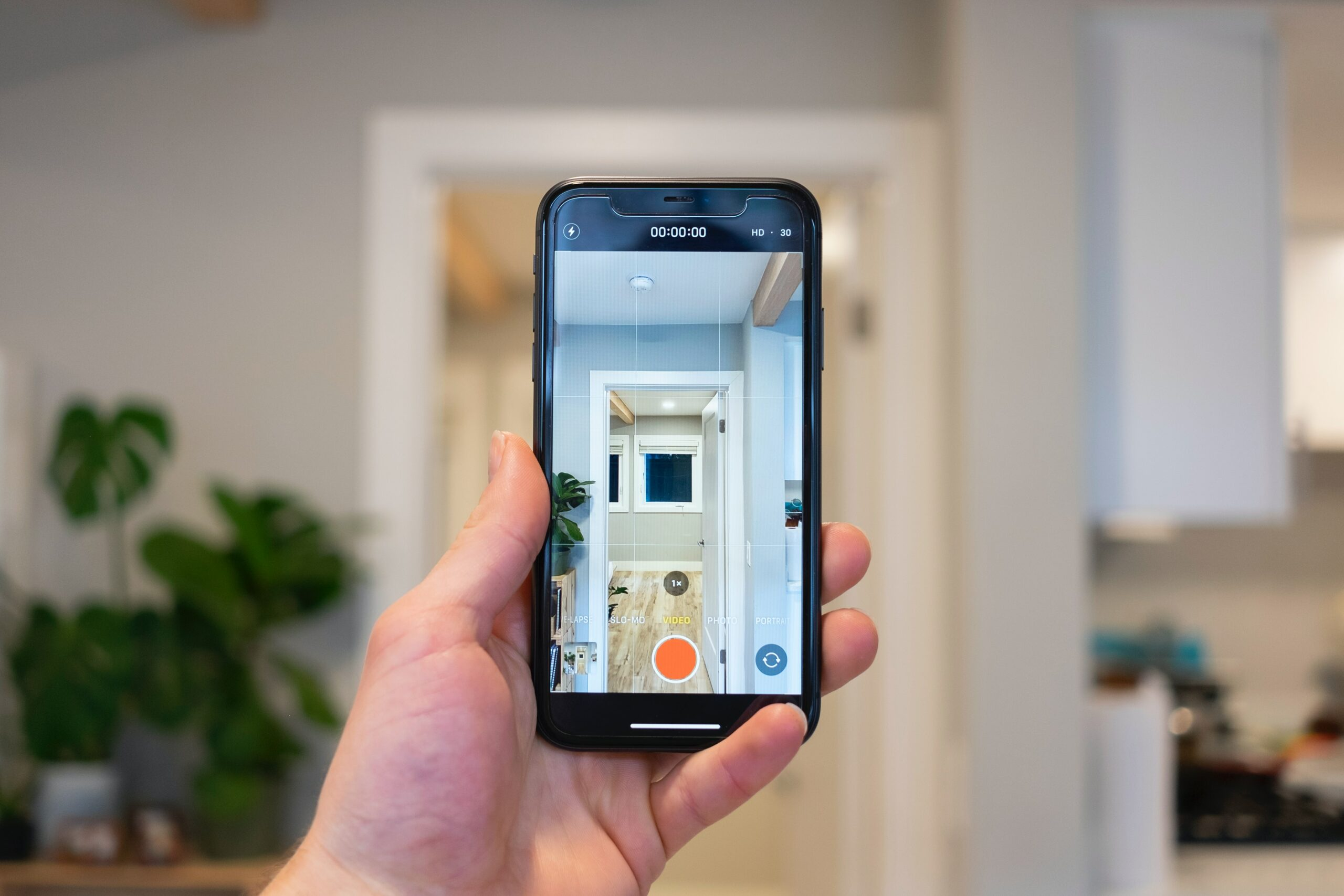A hand using a phone to take a picture of a hallway - one of Marie's 10 home staging tips