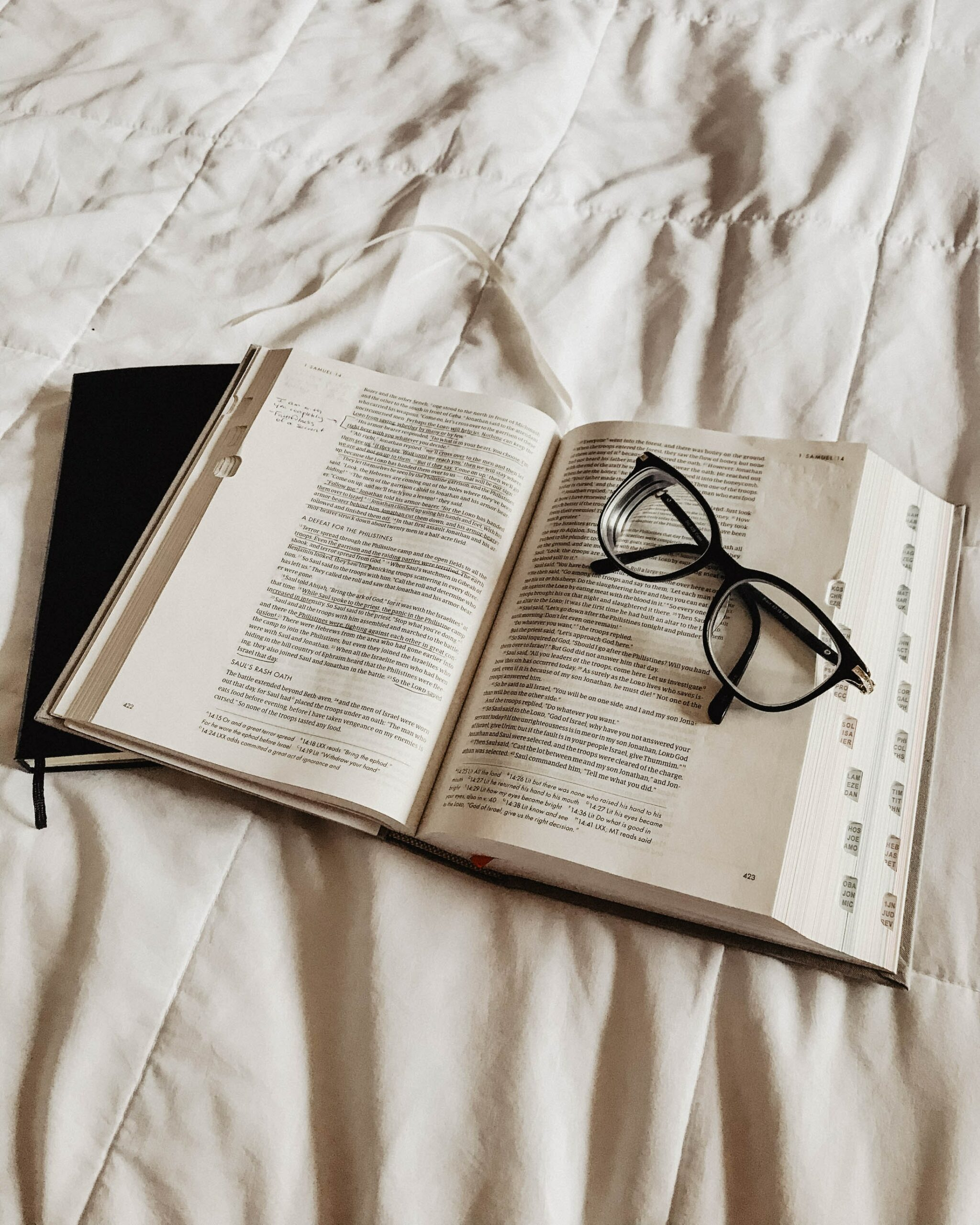 A bible with glasses resting on top of it - keeping a faith, a tip for a happier life