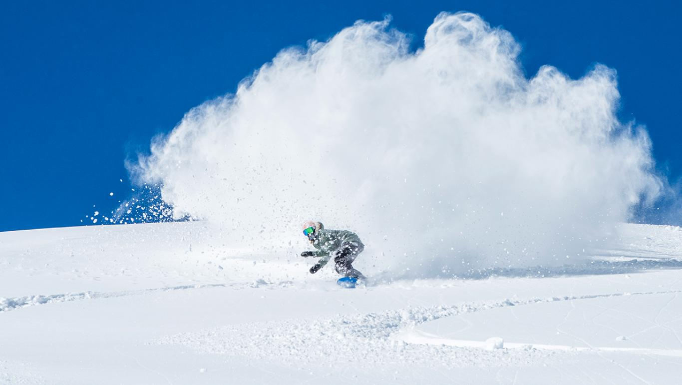 A snowboarder riding down Mt bachelor - one of the things to do in Bend, Oregon