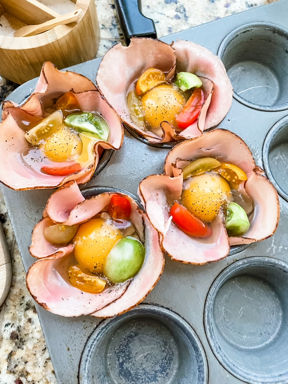 The muffin tin lined with ham and filled with the egg mixture