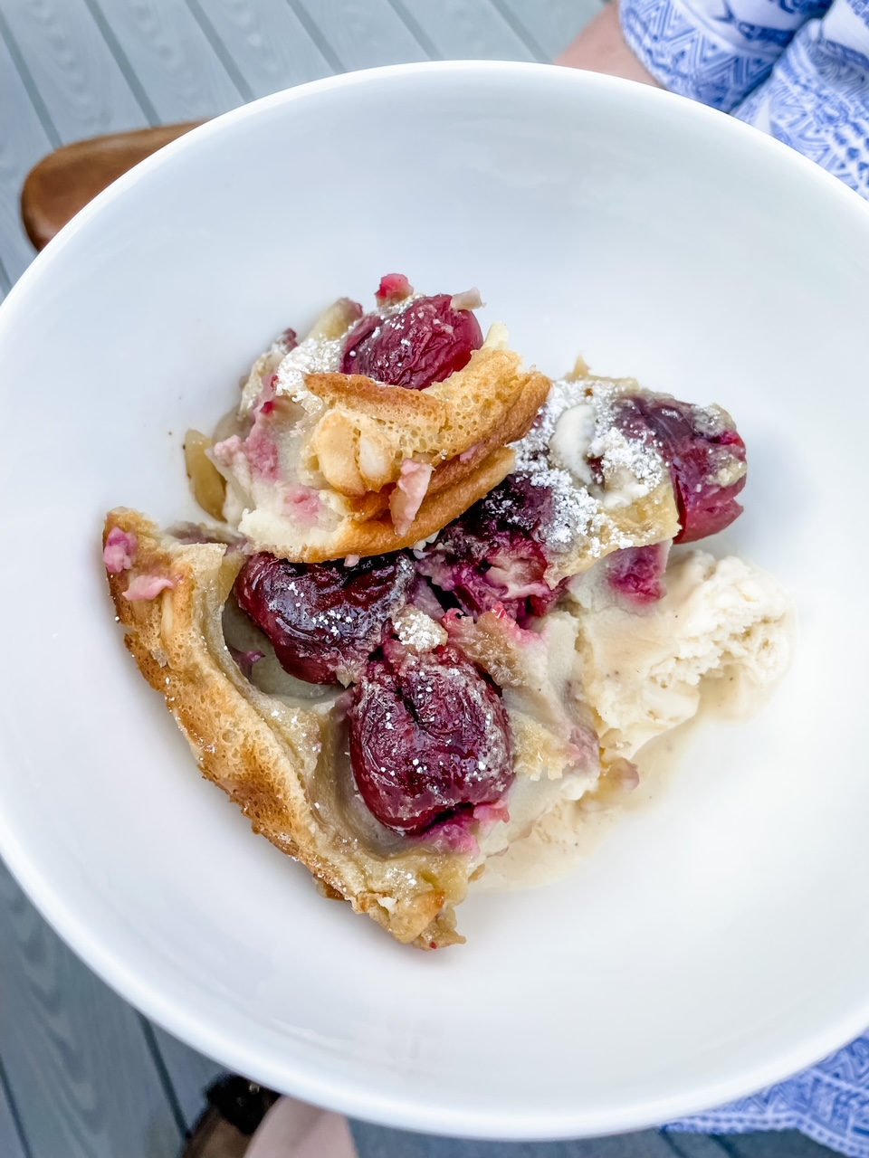 A slice of the Fresh Cherry Clafoutis in a white bowl