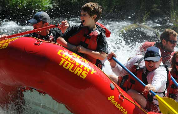 A Sun Country Tour raft filled with passengers with oars and wearing life vests