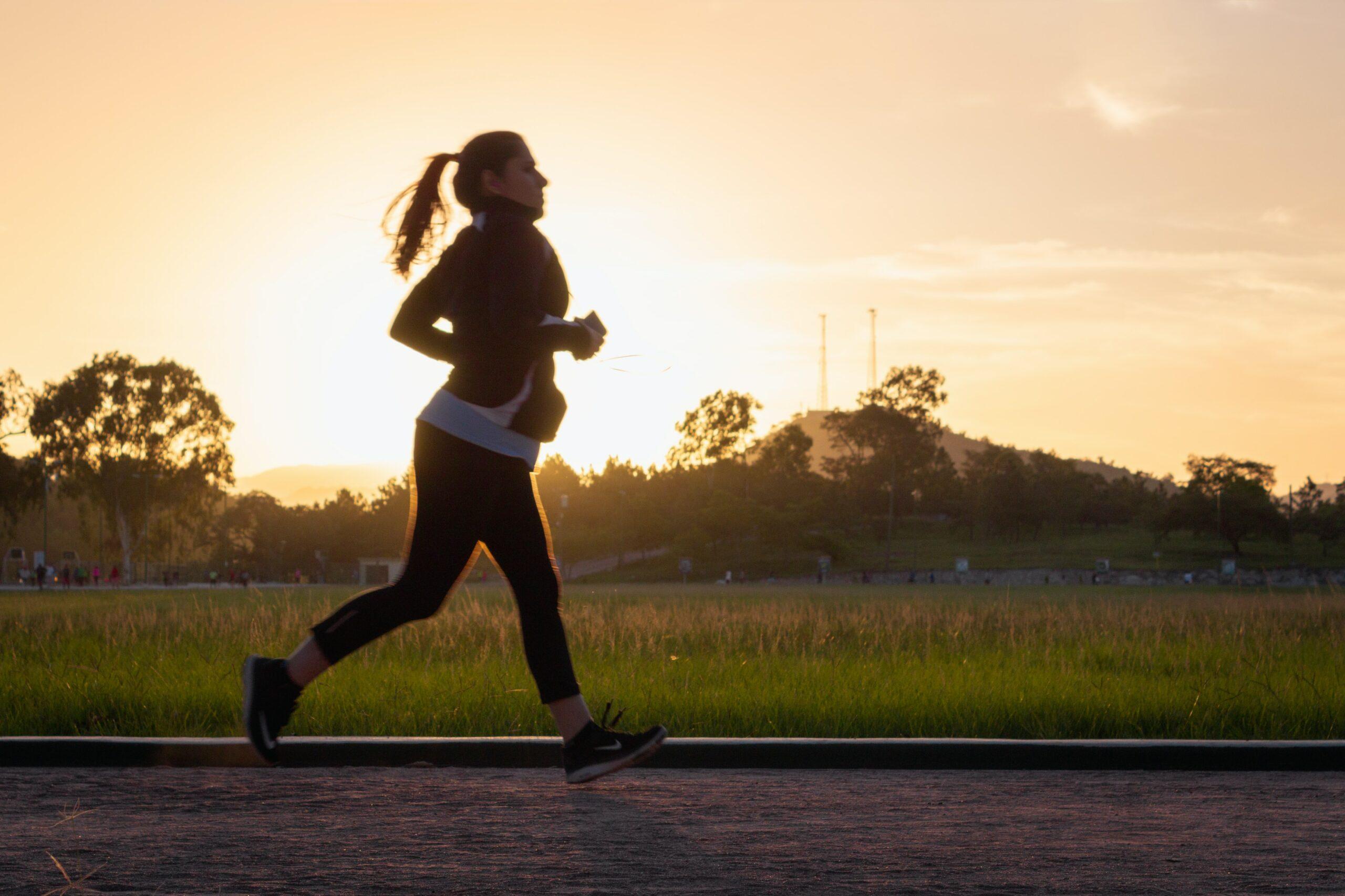 A woman jogging along a sunset