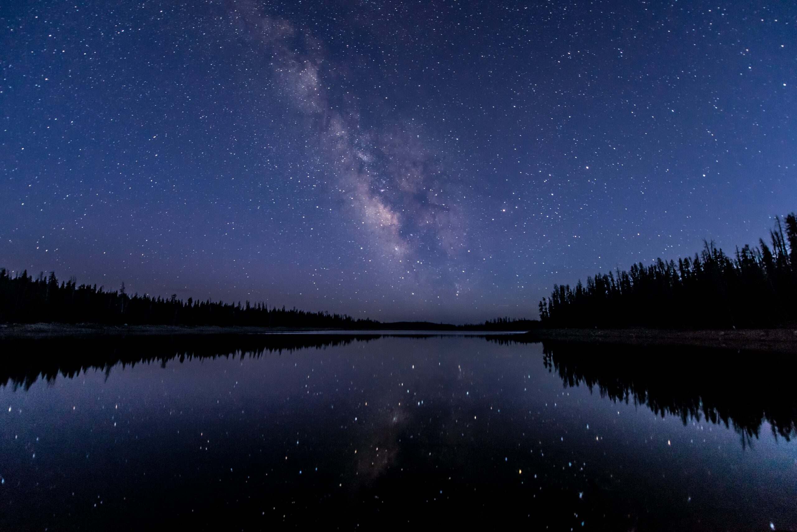 A night sky above a river and forest