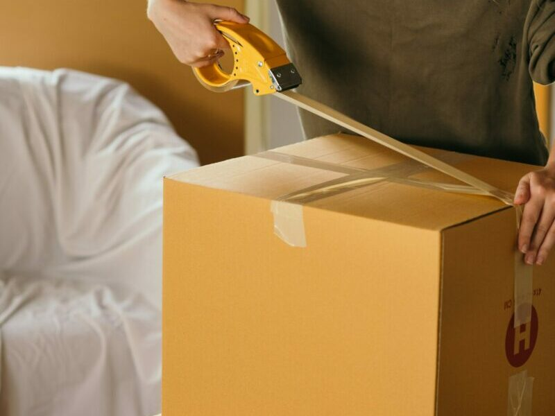 A woman taping a cardboard box shut