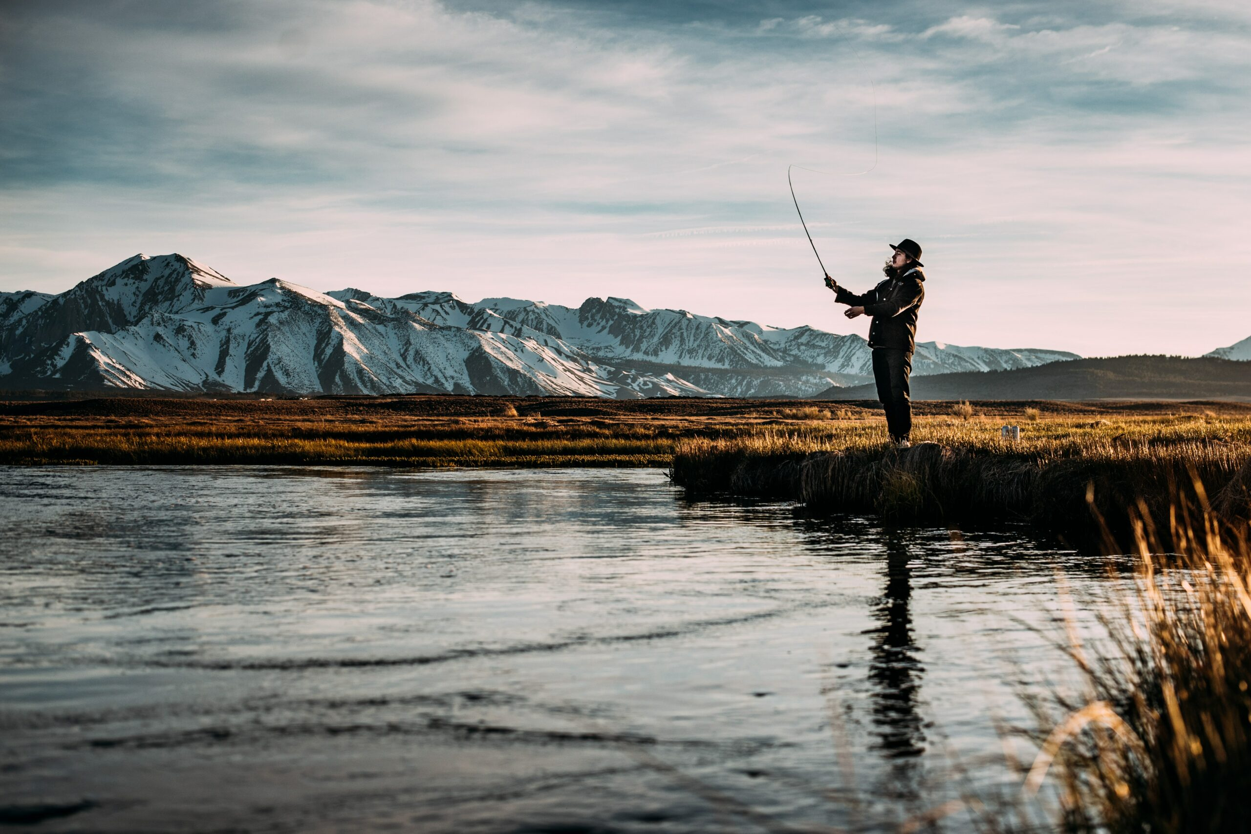 A man flyfishing with a mountain in the background - one of the things to do in Bend, Oregon